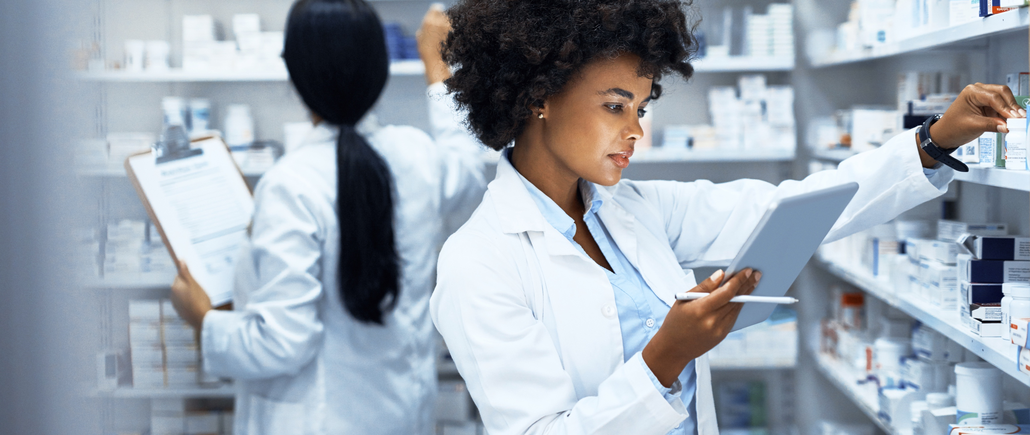 young woman doing inventory in a pharmacy on a digital tablet with her colleague in the background